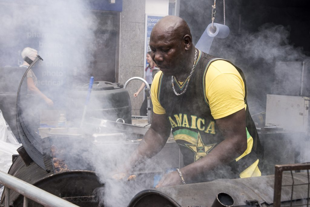 Jamaican chef cooking jerk chicken - Food Street Market Reading, UK - June 2nd, 2018